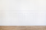 Empty white room with parquet floor and wood trimmed wall
