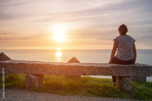 Chica joven observando el atardecer sobre el mar en soleda