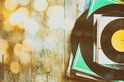 Enregistrements pile sur la table en bois et les fuites de lumière vintage Poster