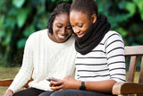 Two teenage african girlfriends socializing on phone.