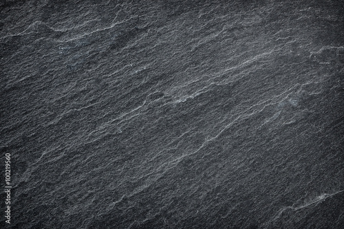 Dark grey / black slate background or texture.