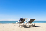 Fototapety Two deck chairs and hat, relaxing on the beach, sunny