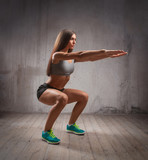 attractive sportswoman doing squats in brutal interior