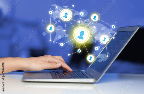 Close up of hand with laptop and social media icons