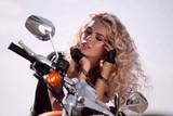 Biker girl in helmet sitting on vintage custom motorcycle.