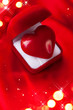 Valentine heart in gift box on red silk background