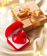 Valentine heart and gift box on golden silk background