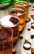 Obrazy na płótnie, fototapety, zdjęcia, fotoobrazy drukowane : Four beers with pistachios on a wooden table.