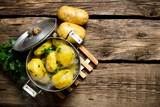 Fototapety Boiled potatoes with herbs on wooden table . Free space for text.