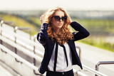 Young fashion business woman in sunglasses walking on city street