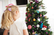 Little girl decorating Christmas tree before new year's eve.