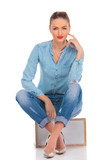 woman pose in studio seated with hand on knee touching face