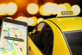 Fototapety Calling taxi from mobile phone concept, yellow cab transportation network, modern smartphone with app for online taxi ordering service on screen, car with taxi sign at roof on street at night