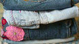 Many different denim clothing. Shorts, trousers, jacket of blue color.