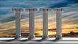 Four ancient pillars with sunset sky background.