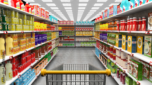 Supermarket interior with shelves full of various products and empty trolley basket