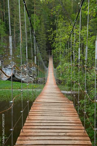 Obraz na Plexi Wooden suspension bridge over the river in the forest