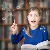 Fototapety Mädchen mit einem Buch mit fliegenden Buchstaben