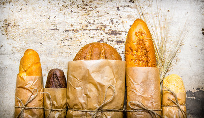 Fresh bread wrapped in paper. On rustic background.