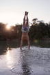 man doing a handstand on river