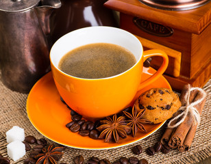 Coffee cup and coffee beans on a wooden table and sack backgroun