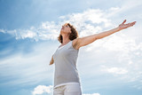 breathing outside - zen middle aged yoga woman opening up her chakra with arms raised,practicing meditation for freedom over summer blue sky,low angle view - 100757146