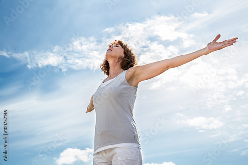 Papiers peints Ecole de Yoga breathing outside - zen middle aged yoga woman opening up her chakra with arms raised,practicing meditation for freedom over summer blue sky,low angle view