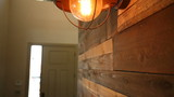 Reclaimed Wood Residential Wall Rise to Light. camera rises up a wall in a modern industrial style home with a reclaimed wood wall to reveal and older style light