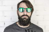 Hipster. Portrait of a bearded young man with green sunglasses