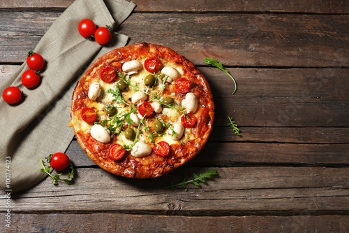 Foto op Canvas Pizzeria Delicious pizza, fresh vegetables and cotton napkin on wooden background, close up
