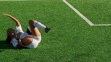 An injured female soccer player motions for the ref to give her opponent a red card