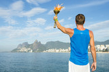 Fototapety Athlete in athletic uniform standing with sport torch in front of Rio de Janeiro Brazil skyline at Ipanema Beach