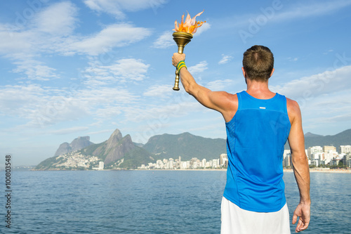 Papiers peints Rio de Janeiro Athlete in athletic uniform standing with sport torch in front of Rio de Janeiro Brazil skyline at Ipanema Beach