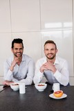 Smiling gay couple having breakfast