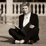 Young business woman with a folder sitting on sidewalk