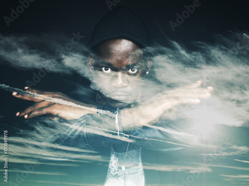 Double exposure of man gesturing and wearing hoodie and cloudscape - 100849978