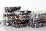 Pilhas com grandes quantidades de blísteres de comprimidos, em um fundo branco.