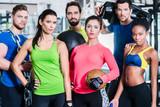 Fototapety Gruppe Frauen und Männer im Fitnessstudio beim Sport stehen beieinander mit Geräten und Hanteln