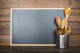 Pizarra vacía con espacio para texto sobre fondo de madera y utensilios de cocina