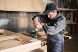 Carpenter assembles wooden furniture, focus on the hand drill