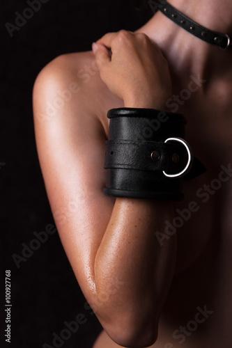 schöne nackte Frau mit ledernen Handgelenks Fesseln