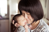 Asian mother holds her  newborn baby - 100961362