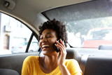 Fototapety Laughing young woman in a car talking on mobile phone