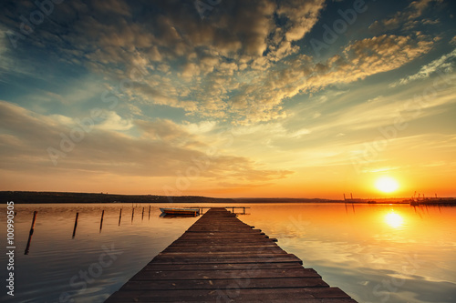 Boat and jetty on lake with a reflection in the water at sunset