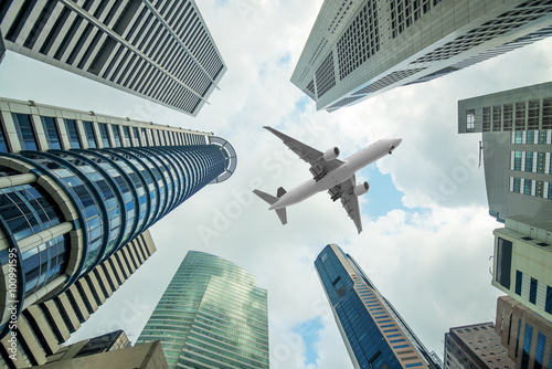Poster Tall city buildings and a plane flying overhead in morning