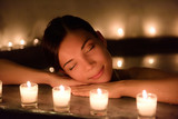 Beautiful young woman relaxing in jacuzzi hot tub at spa. Attractive female tourist is surrounded with lit candles. Smiling woman with eyes closed is pampering herself during vacation.