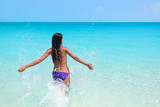 Young woman enjoying herself in sea during summer holidays. Exhilarated female is in bikini. Tourist with arms outstretched is on her vacation at beach.