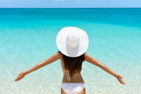 Woman on Beach standing with arms outstretched against turquoise sea. Rear view of female wearing white sunhat and bikini. Carefree tourist is enjoying vacation at beach.