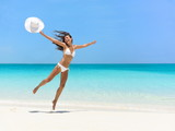 Carefree young woman jumping at beach during summer vacation. Full length of exhilarated female in white bikini. Tourist with arms outstretched is enjoying holidays on sea.