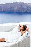 Beautiful young woman relaxing on couch at seaside resort terrace. Attractive female is wearing white sundress. Female with hands behind head is relaxing on lounge chair against sea and mountain.